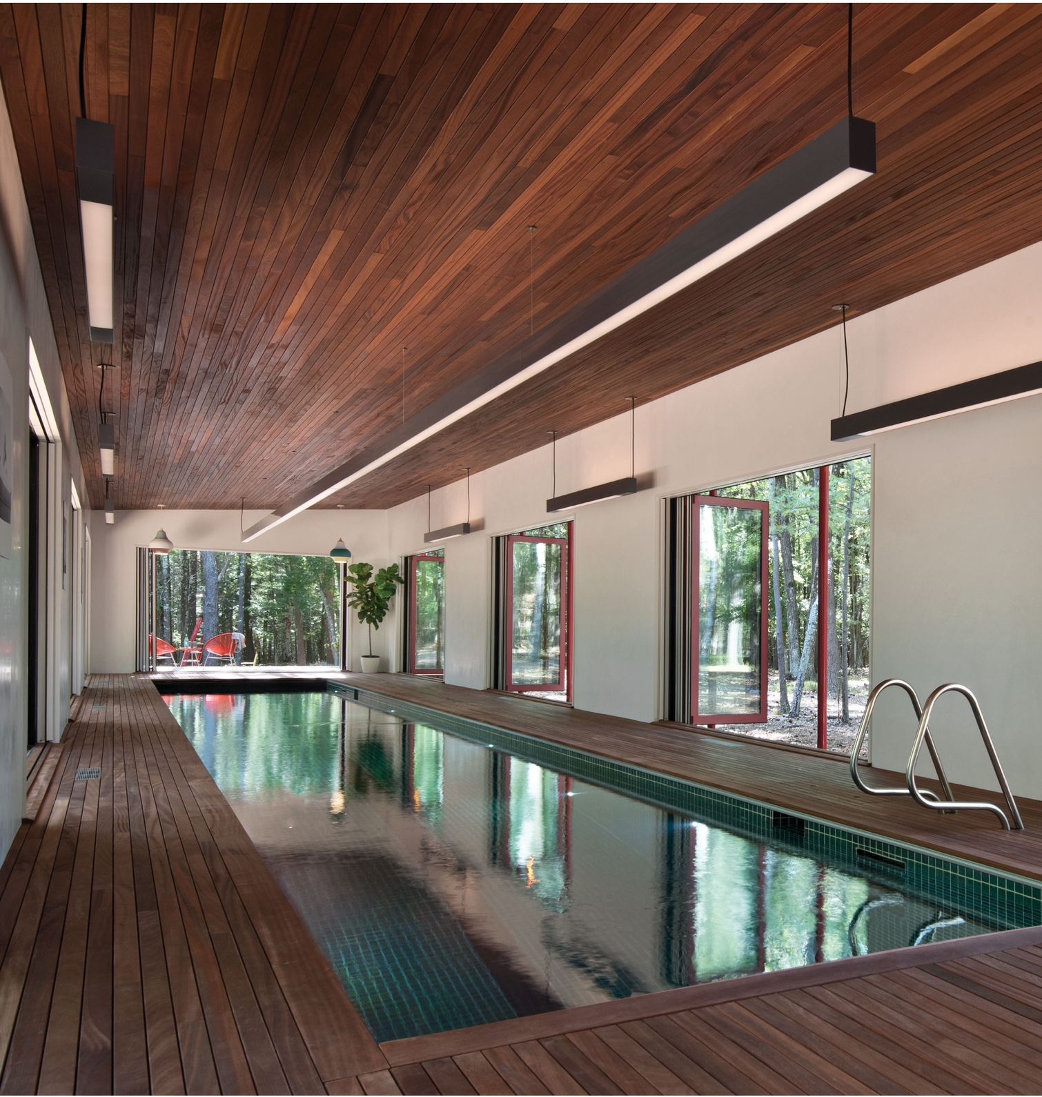 An indoor pool next to a wall of open folding doors from The Folding Door Store.