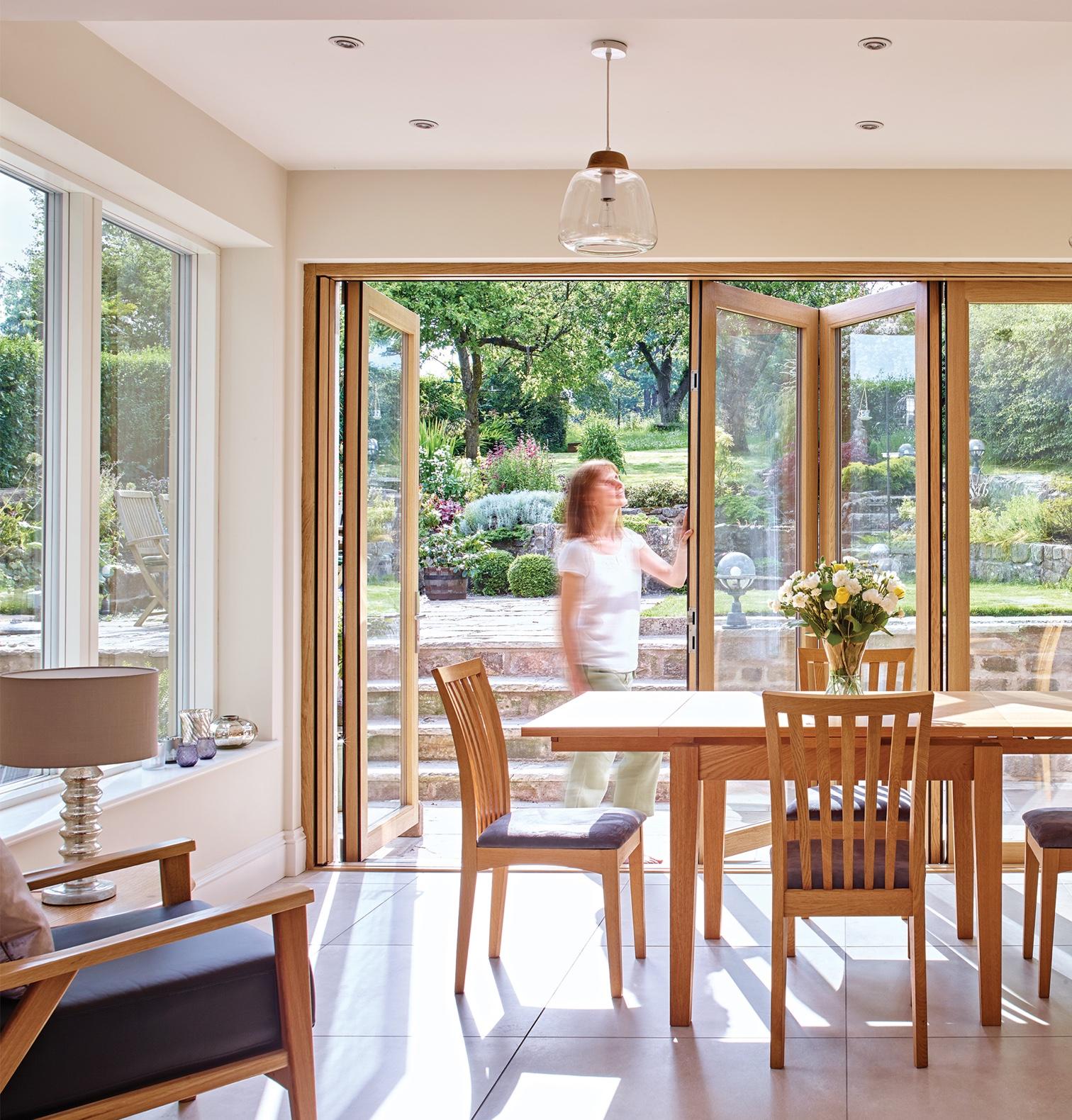 Woman opening patio door by dining room