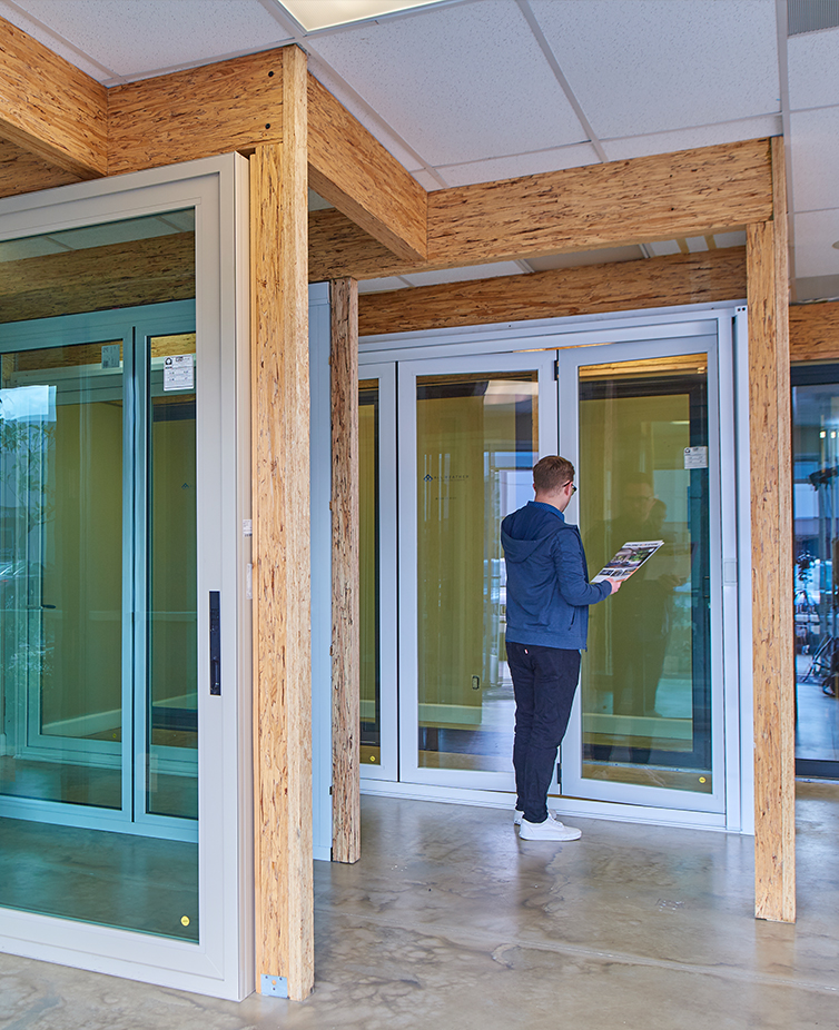 A man holding a brochure looks at sample doors at a Folding Door Store showroom.