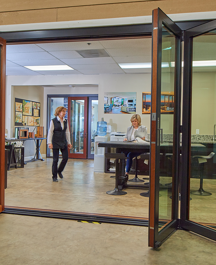 One woman is walking and one woman is sitting at a table at a Folding Door Store showroom.