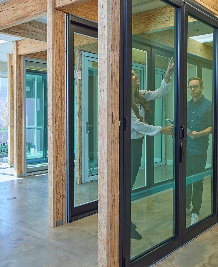 A man and a woman look at a sample folding door at a Folding Door Store showroom.