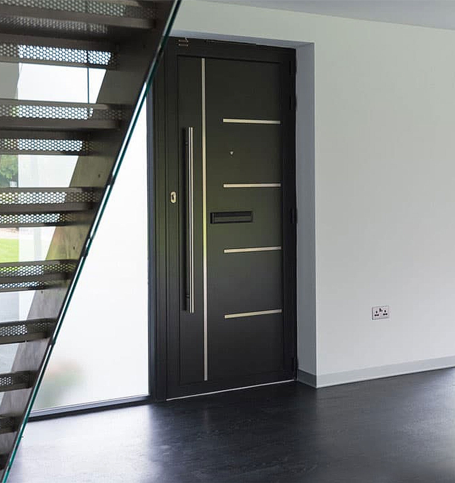A black steel entry door from The Folding Door Store in Southern California.
