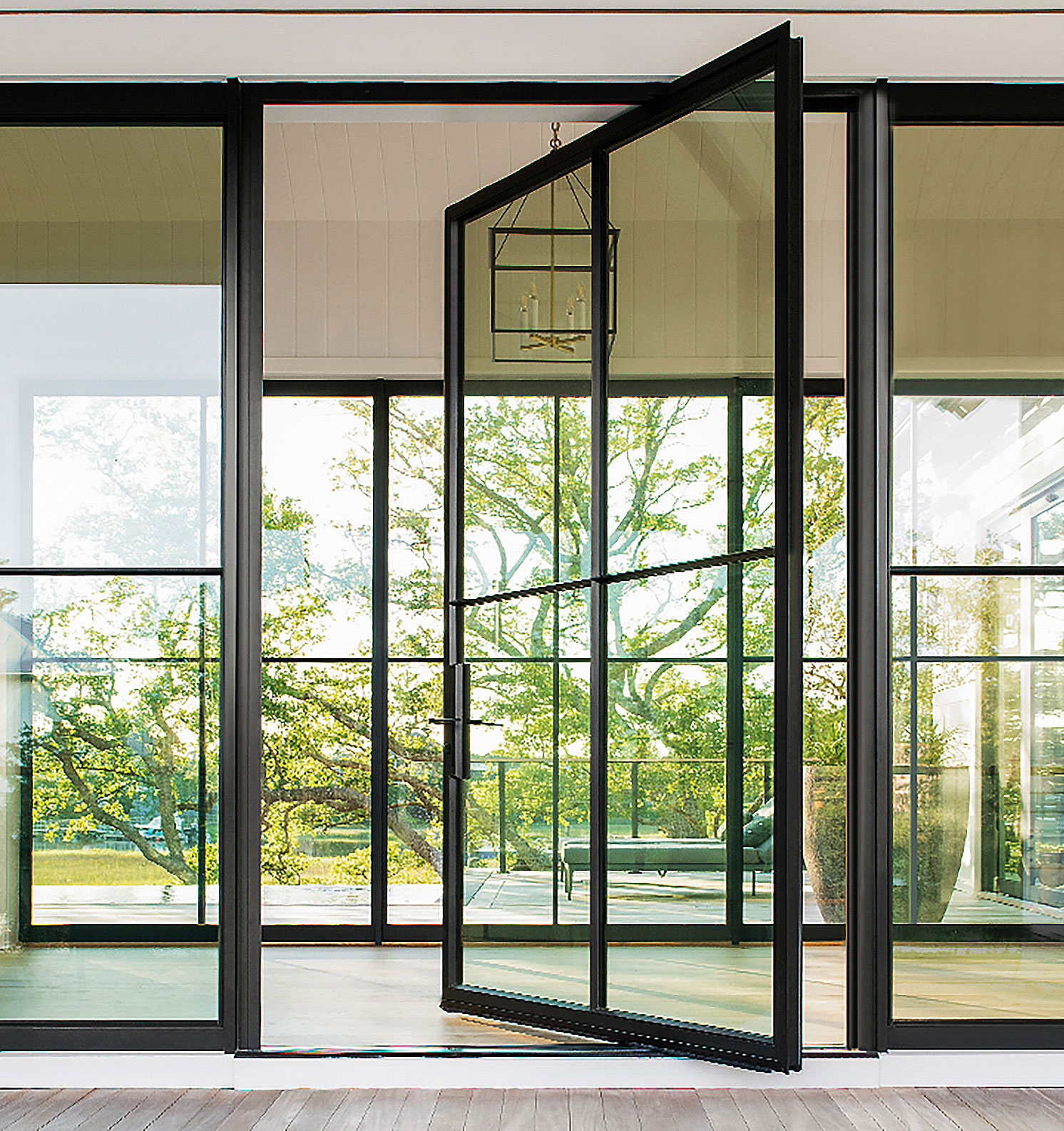A glass entry door from The Folding Door Store opening into a foyer.
