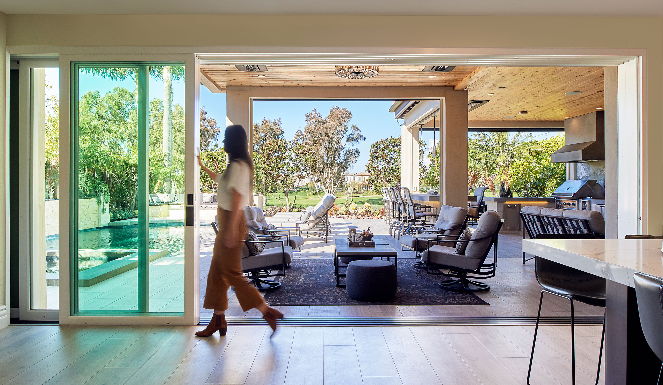 A woman opening multi-slide exterior glass sliding doors from The Folding Door Store.