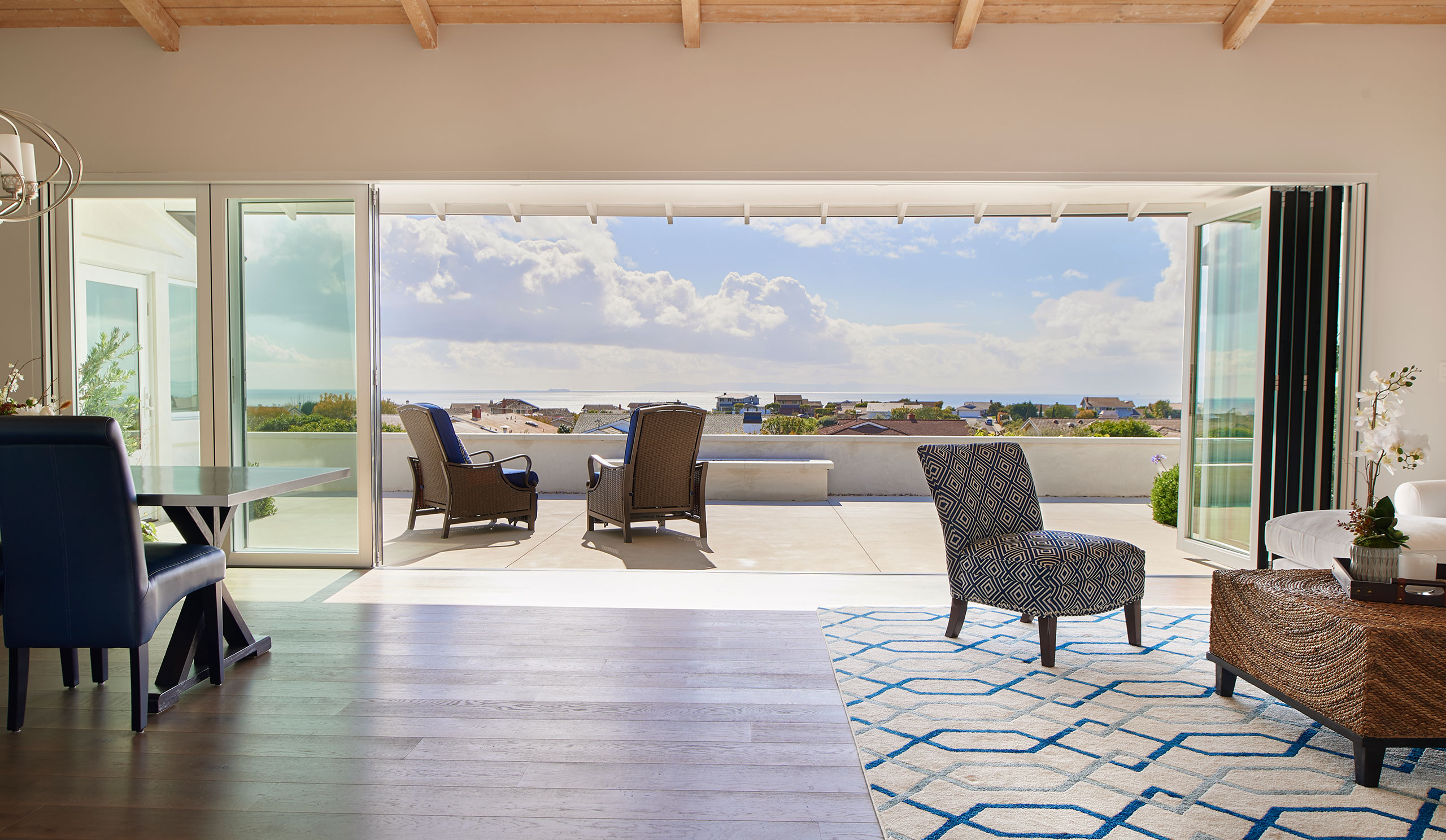 Folding glass doors open easily to add space and bring fresh air in by The Folding Door Store.
